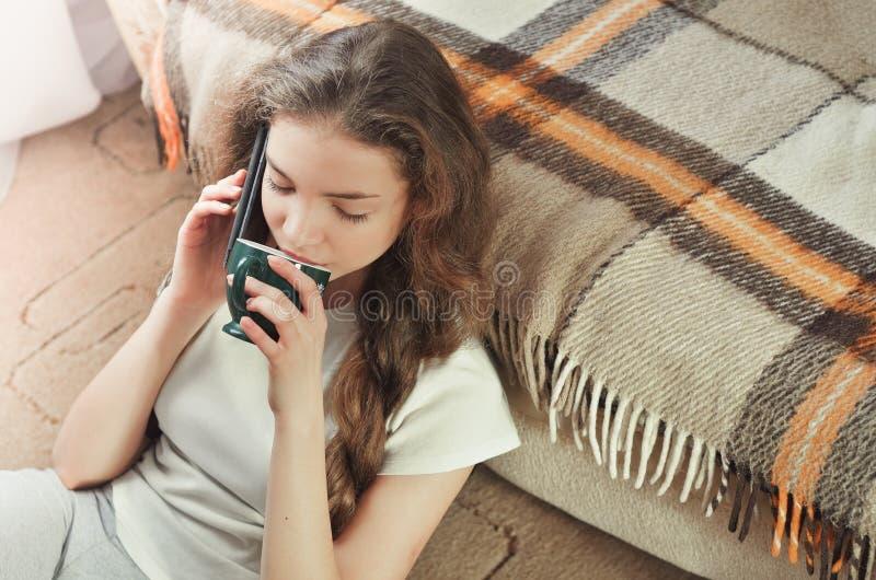 Nettes Brunettemädchen, das am Handy beim Sitzen nahe Couch spricht stockfotografie