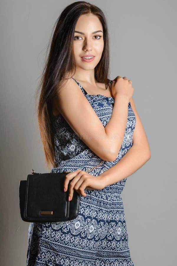 Nettes Brunettemädchen mit dem langen flüssigen Haar, das schwarze Handtasche hält stockbild
