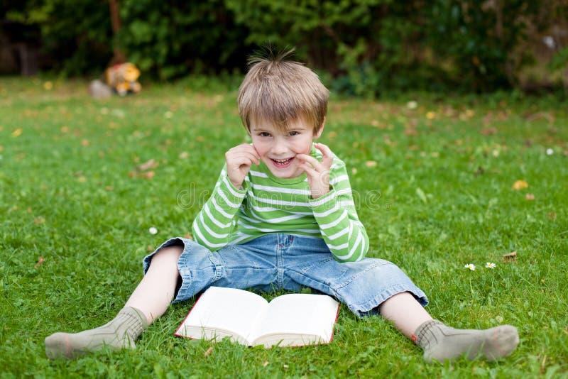 Nettes Buch des kleinen Jungen Leseauf dem Gras lizenzfreie stockfotos