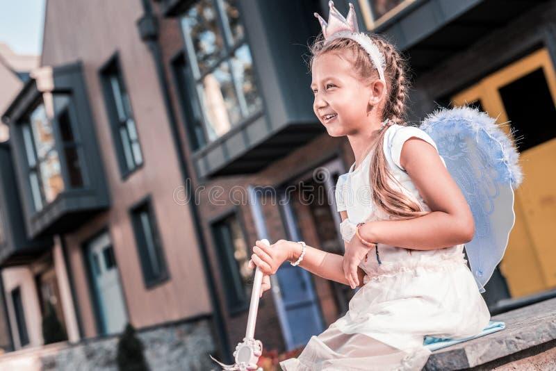 Nettes dunkelhaariges Mädchen, das feenhafte Flügel und gehende Außenseite der kleinen Krone trägt stockfoto