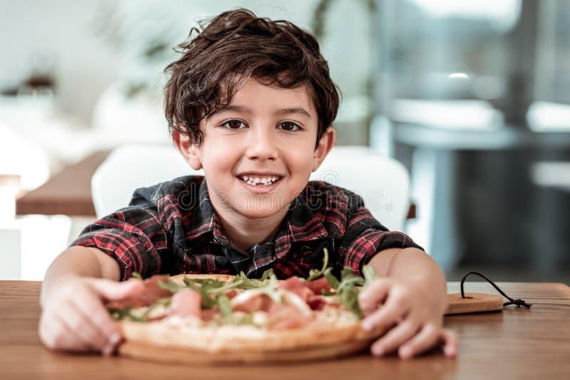 Nettes dunkelhaariges Sohngefühl aufgeregt, Pizza mit seinem Vater essend stockbilder