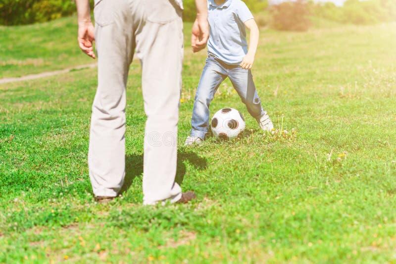 Nettes Enkelkind und Großvater, die zusammen Fußball spielt lizenzfreie stockbilder