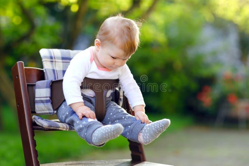 Nettes entzückendes Baby, das draußen im Hochstuhl sitzt Beatuiful-Kind von 6 Monaten im Hausgarten, spielend auf warmem lizenzfreie stockbilder