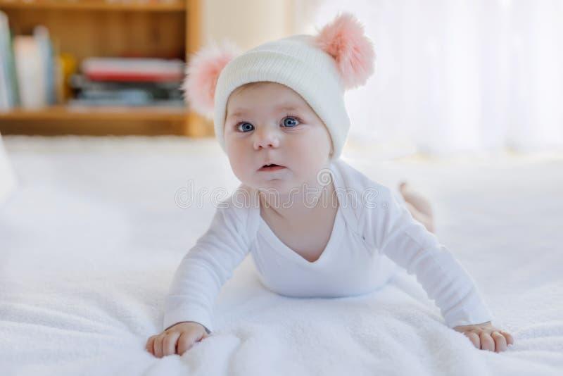 Nettes entzückendes Babykind mit warmem weißem und rosa Hut mit nettem bobbles Glückliches Baby, das Schleichen lernt und betrach stockbild