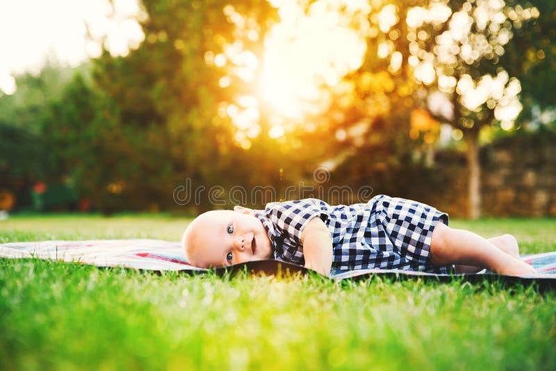Nettes entzückendes Kinderbaby, das auf dem Gras auf Natur liegt stockfoto