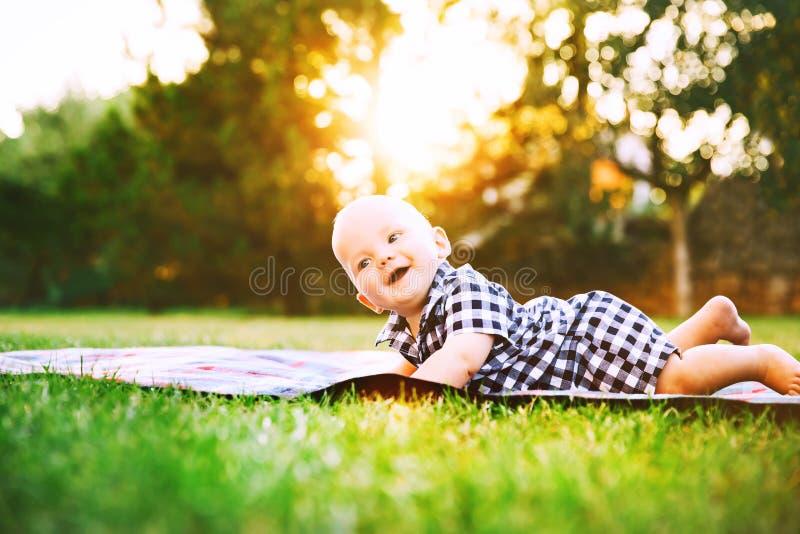 Nettes entzückendes Kinderbaby, das auf dem Gras auf Natur liegt lizenzfreies stockfoto