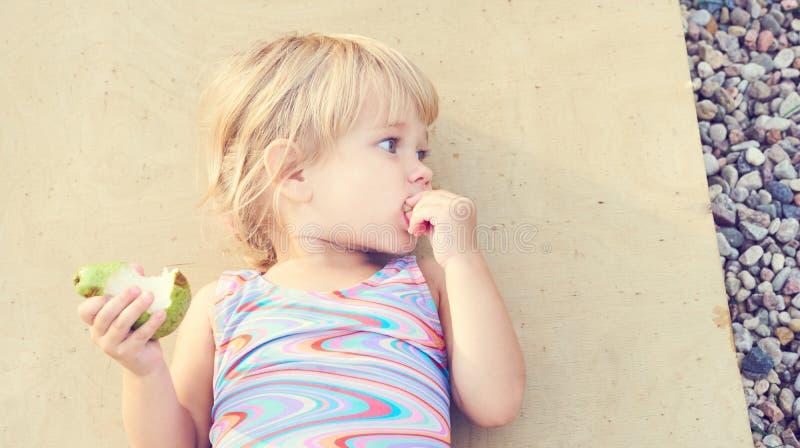 Nettes entzückendes Kleinkindmädchen, welches die frische Birne liegt auf dem Strand isst lizenzfreies stockfoto
