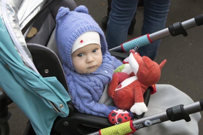 Nettes ernstes Baby, das im Spaziergänger sitzt stockfotos