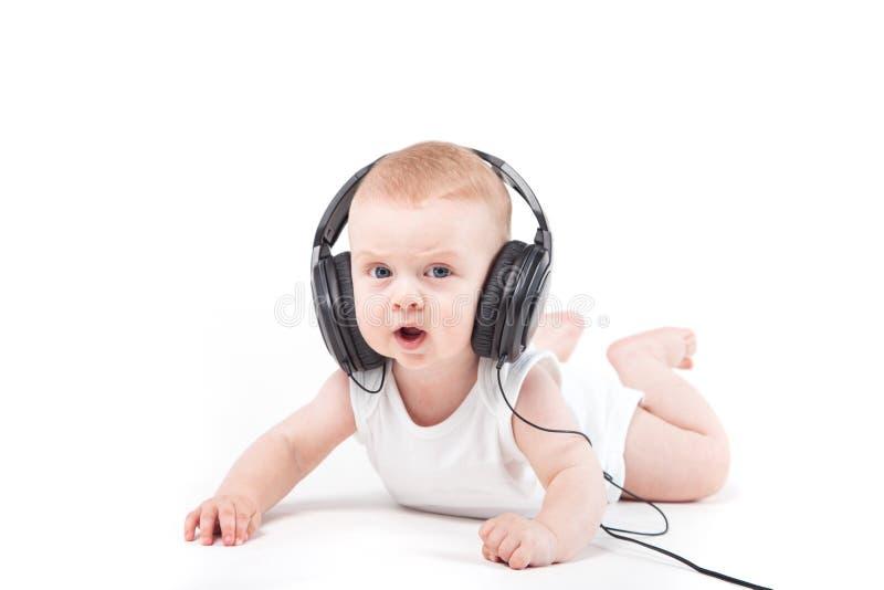 Nettes ernstes Baby liegt mit Kopfhörern stockfoto