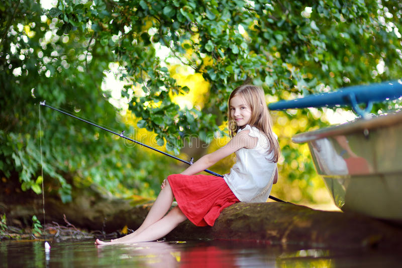 Nettes Fischen des kleinen Mädchens mit einer Angelrute durch einen Fluss stockfotografie