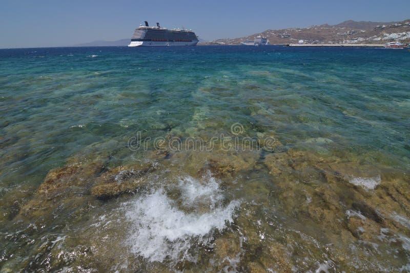 Nettes Foto des Ägäischen Meers, das gegen die Felsen mit einer großen Kreuzfahrt im Hintergrund auf der Insel von Mykonos bricht stockfoto