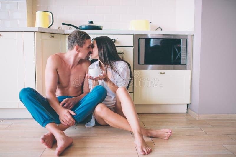 Nettes Foto des Kerls und des Mädchens, die auf Boden in der Küche und im Küssen sitzen Sie halten Beine gekreuzt Leute lehnen si lizenzfreie stockfotografie