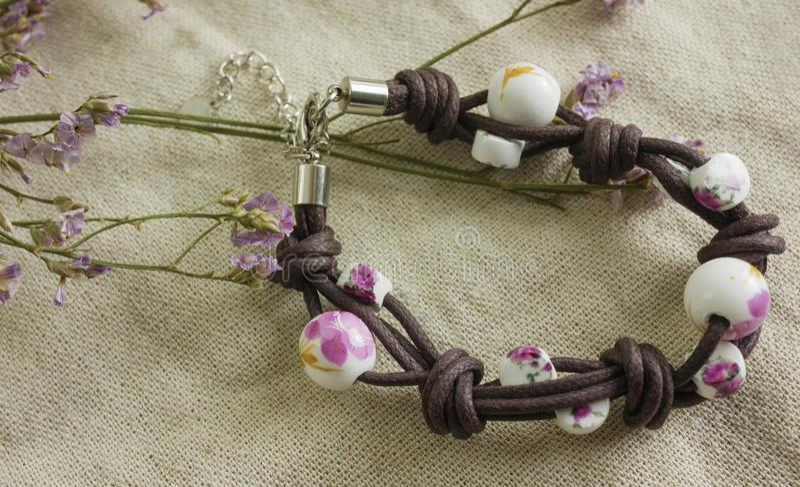 Nettes Frauenarmband auf Gewebe und trockenen Blumen stockfotografie