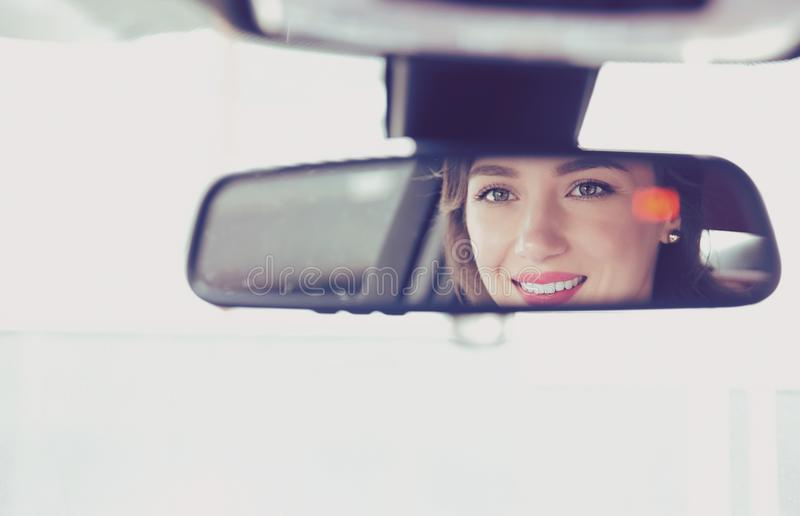 Nettes Frauenautofahren, hintere Ansicht, Reflexion des Gesichtes in einem Spiegel lizenzfreies stockbild