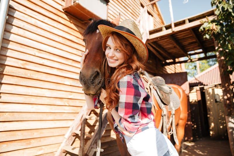 Nettes Frauencowgirl, das ihr Pferd auf Bauernhof steht und umarmt stockfotos