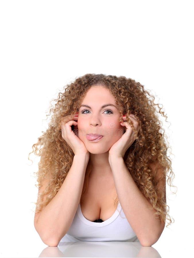 Nettes Frauenhändchenhalten des Porträts unter Kinn und Showzunge stockbild