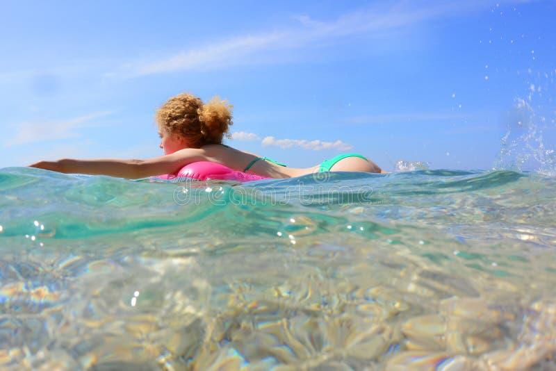 Nettes Frauenschwimmen auf Gummiring stockbild