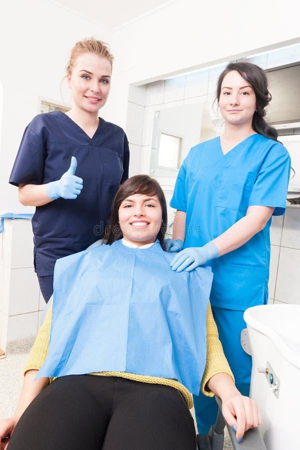 Nettes Frauenzahnarzt thumbup, während Patient und Assistent s sind stockfoto