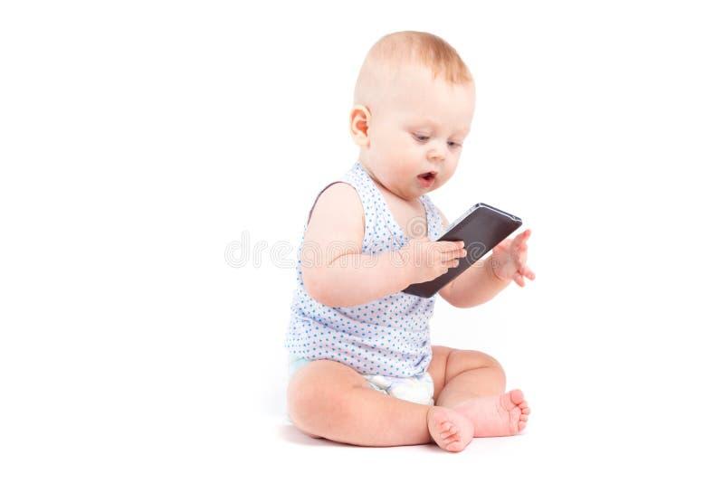 Nettes frohes Baby im blauen Hemd und Windel halten Mobiltelefon stockbilder