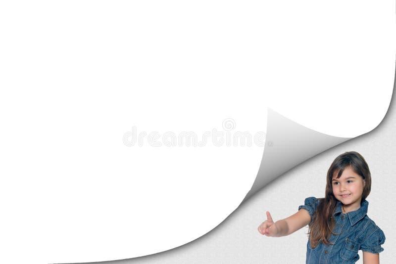 Nettes gebräuntes kleines Mädchen zeigt auf eine Leerseite stockfoto