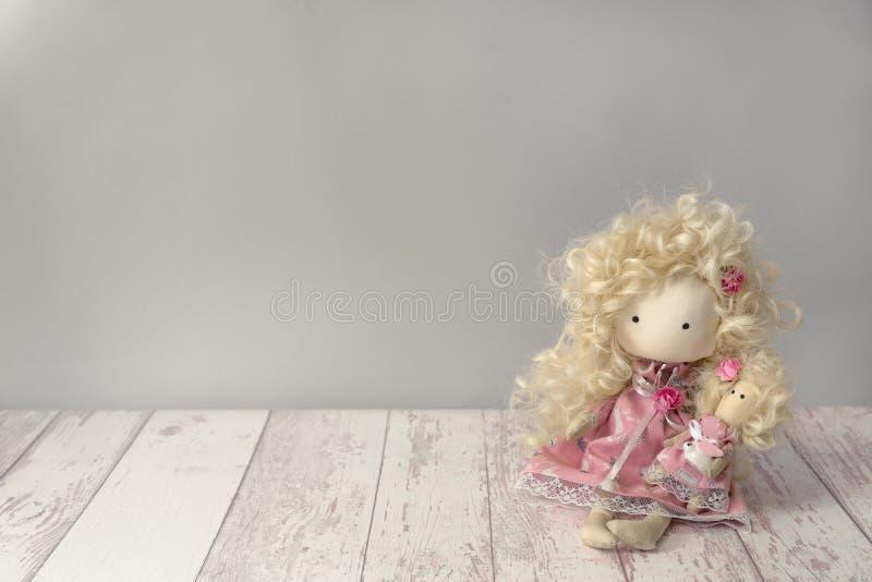 Nettes Gewebepuppenmädchen im rosa Kleid mit weißem Kaninchen sitzt auf einem weißen Holztisch mit copyspace stockbilder