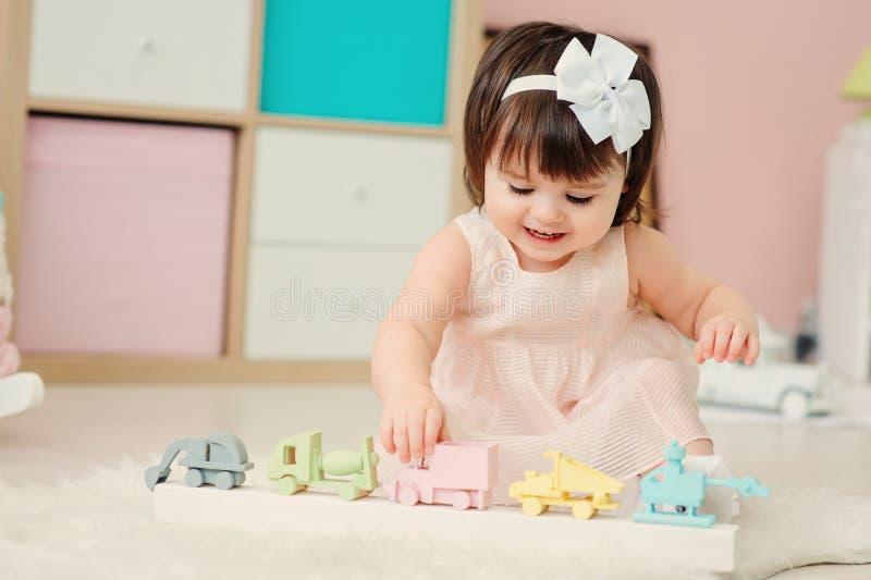 Nettes glückliches einjähriges Baby, das zu Hause mit hölzernen Spielwaren spielt stockfotos
