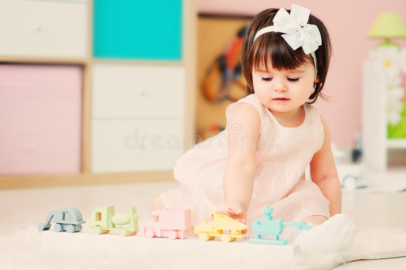 Nettes glückliches einjähriges Baby, das zu Hause mit hölzernen Spielwaren spielt lizenzfreie stockfotografie