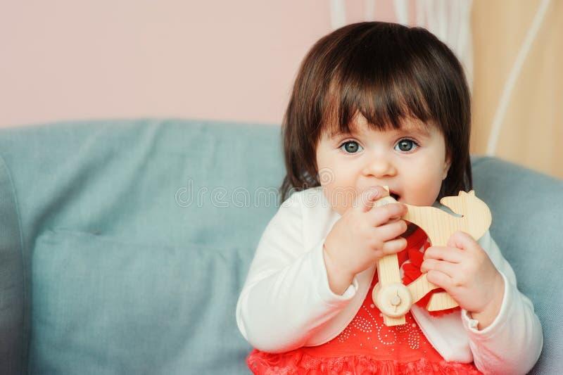 Nettes glückliches einjähriges Baby, das zu Hause mit hölzernen Spielwaren spielt lizenzfreie stockbilder