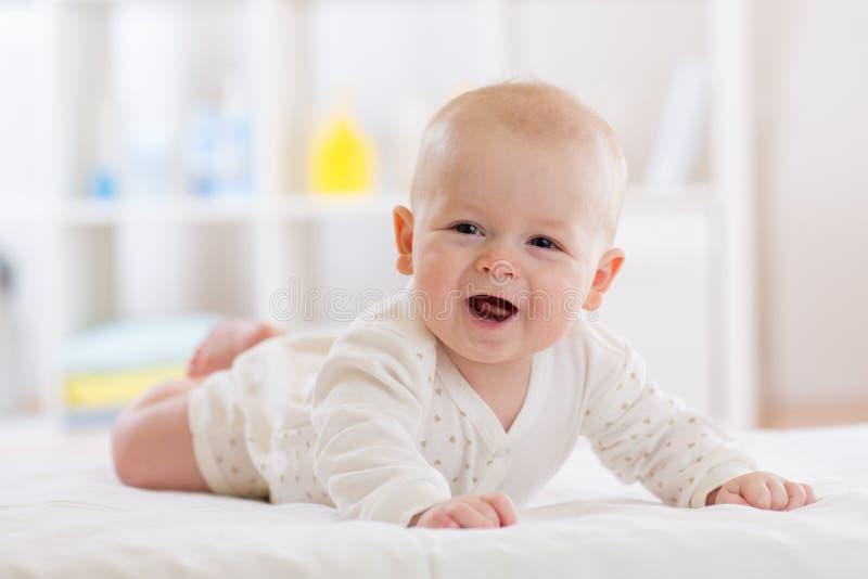Nettes glückliches kaukasisches Baby im weißen Hemd liegt, lächelnd auf Bett lizenzfreies stockbild
