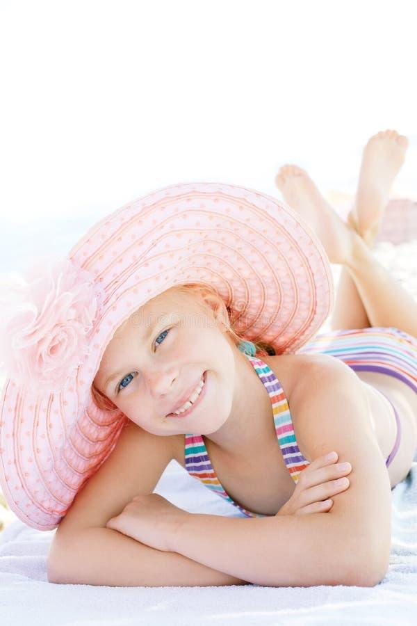 Nettes glückliches Kind, das sich auf deckchair des Strandurlaubsorts hinlegt lizenzfreie stockbilder