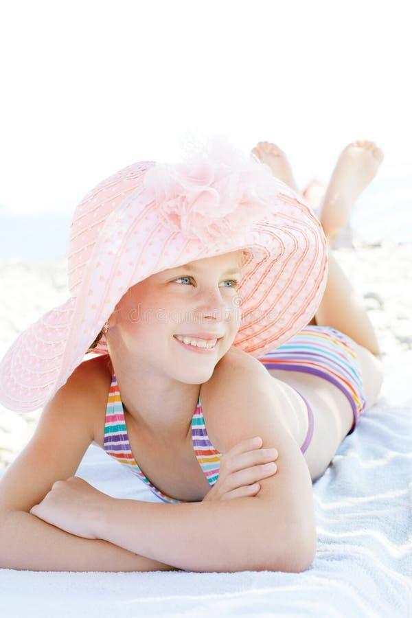 Nettes glückliches Kind, das sich auf deckchair des Strandurlaubsorts hinlegt lizenzfreie stockfotografie