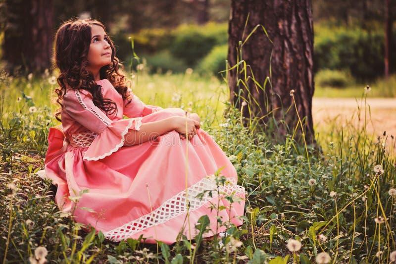 Nettes glückliches Kindermädchen in Märchenprinzessinkleid auf dem Weg im Sommer stockfoto