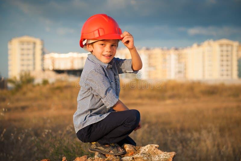 Nettes glückliches Kindertragender Sturzhelm, der auf dem Neubauhintergrund bei Sonnenuntergang sitzt stockfotos