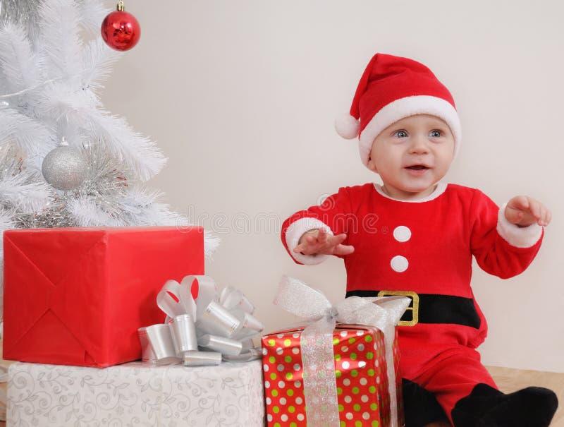 Nettes glückliches kleines Baby in Sankt-Klage mit Geschenken nahe Christm stockbilder