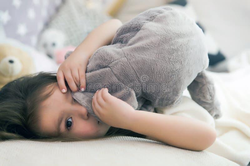 Nettes glückliches kleines Mädchen, das herein schlafen und träumen und Bett, das ihr Spielzeug umarmt stockbild
