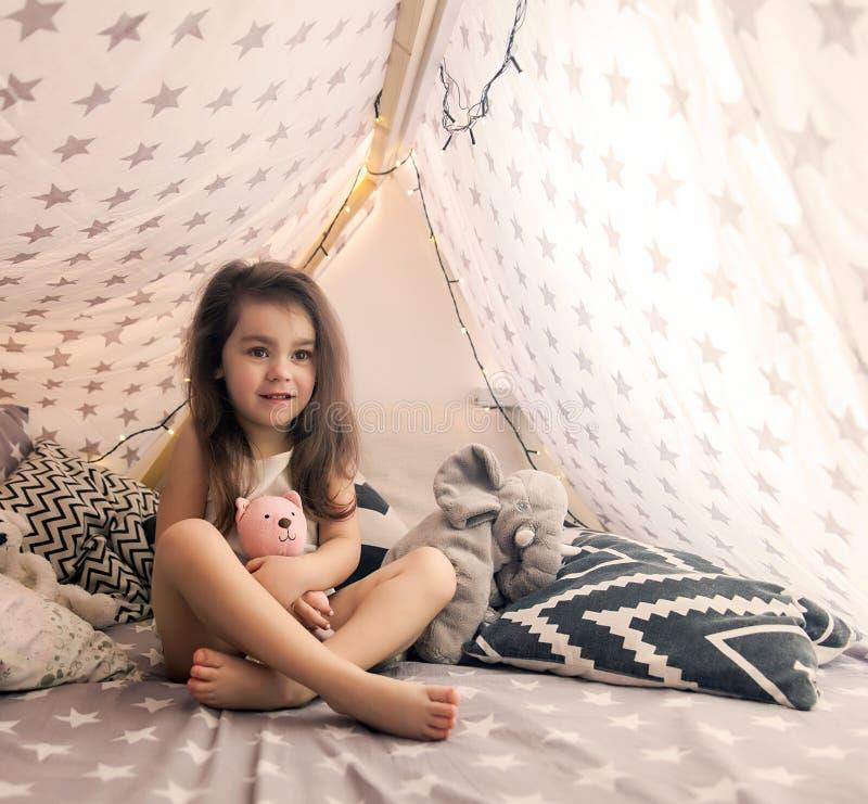 Nettes glückliches kleines Mädchen, das mit Spielwaren spielt und im Tipi und im Bett träumt Schließen Sie herauf Foto des glückl stockfotos