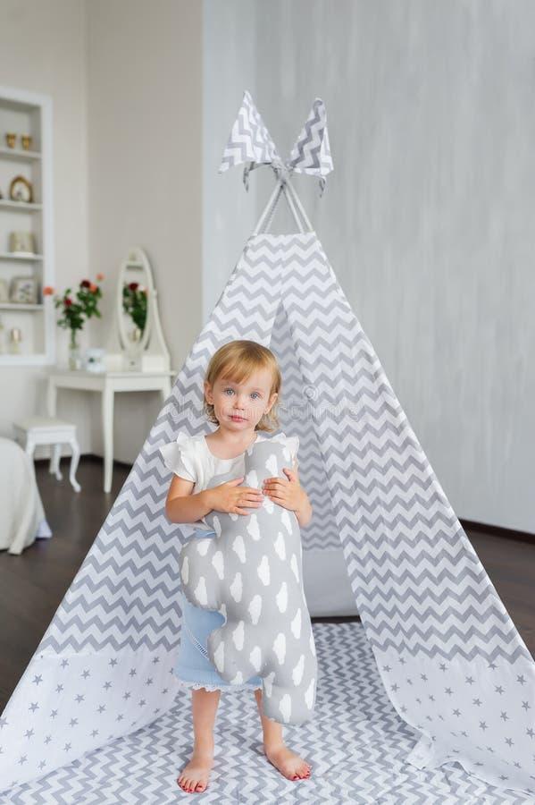 Nettes glückliches kleines schönes Mädchen, das im Tipi am Kindertagesstättenraum steht stockfotografie