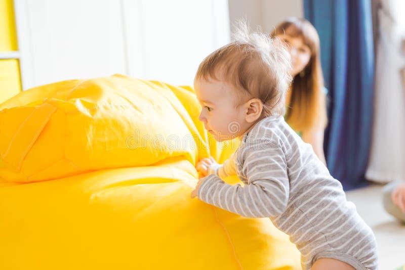 Nettes glückliches lachendes Baby, das auf weißem Schlafzimmer spielt stockfotografie