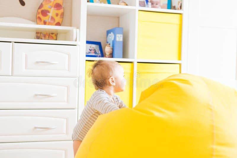 Nettes glückliches lachendes Baby, das auf weißem Schlafzimmer spielt lizenzfreies stockbild