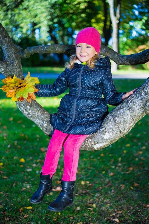 Nettes glückliches Mädchen, das auf Baumast im Herbstpark sitzt lizenzfreie stockfotos