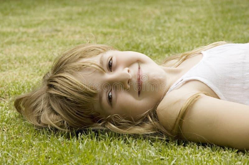 Nettes glückliches Mädchen, das auf Gras lächelt lizenzfreie stockfotografie
