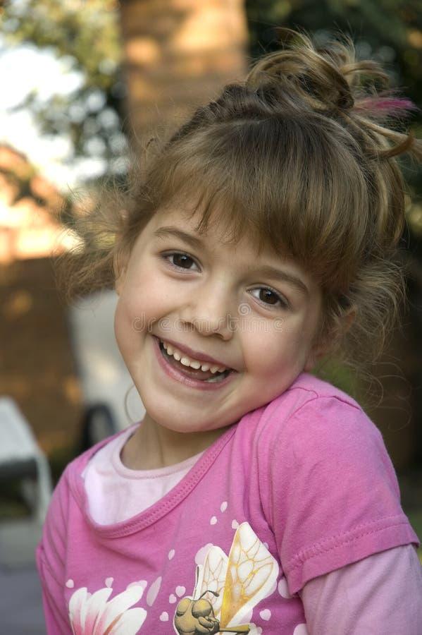 Nettes glückliches Mädchen, das im rosafarbenen Hemd lächelt stockfoto