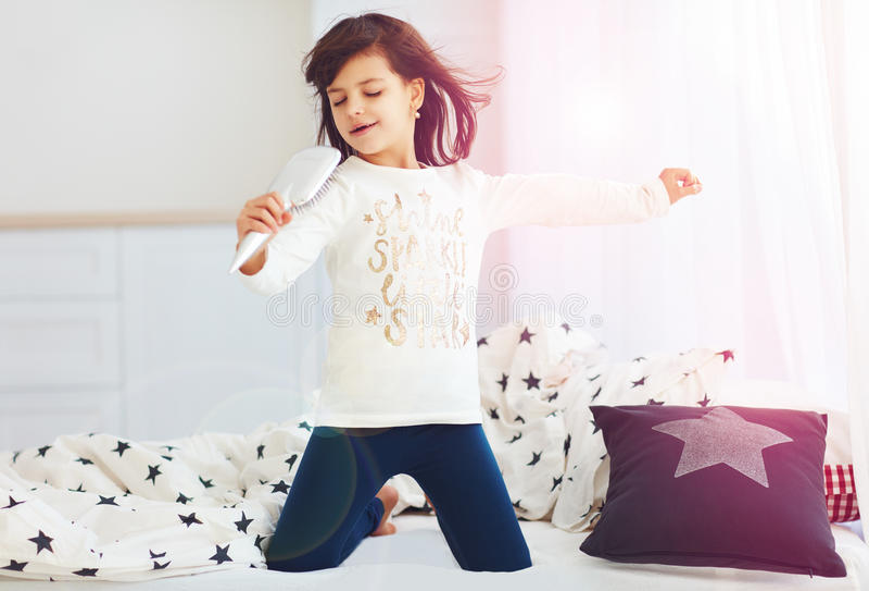 Nettes glückliches Mädchen, das morgens in das Sonnenlicht der Mikrofonbürste zu Hause singt lizenzfreies stockfoto