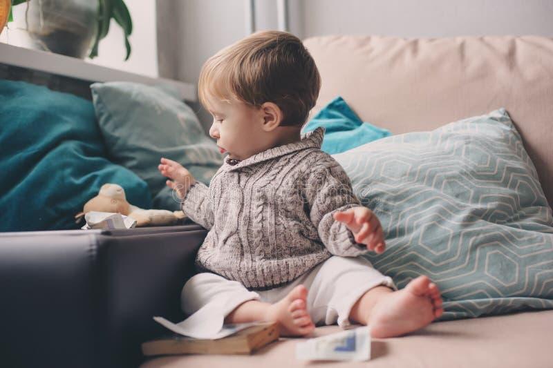 Nettes glückliches 11-monatiges Baby, das zu Hause, Lebensstilgefangennahme im gemütlichen Innenraum spielt stockbilder