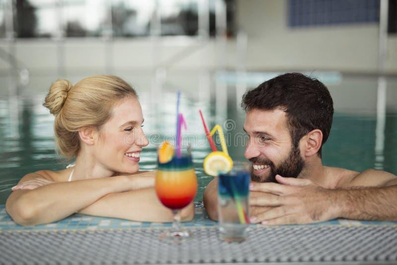 Nettes glückliches Paar, das im Swimmingpool sich entspannt stockbilder