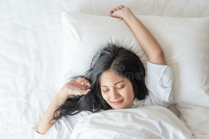 Nettes hübsches Asiatinlächeln und glücklich auf Bett im Schlafzimmer stockbild