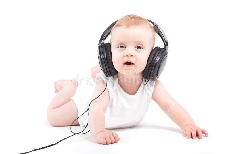 Nettes hübsches Baby im weißen Hemd und in den Kopfhörern auf Kopf stockfoto