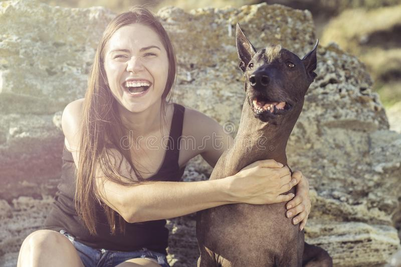 Nettes hübsches junges Mädchen, das ihr Hund-xoloitzcuintli auf dem stoun Strand bei Sonnenuntergang sitzt und umarmt stockbild