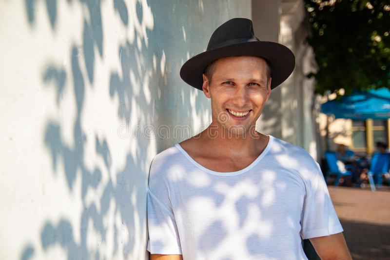 Nettes hübsches lächelndes Gestikulieren des jungen Mannes, Kamera über weißem Hintergrund betrachtend stockbild