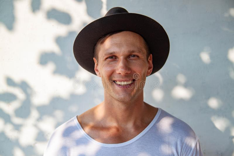 Nettes hübsches lächelndes Gestikulieren des jungen Mannes, Kamera über weißem Hintergrund betrachtend lizenzfreie stockfotografie